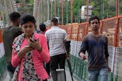 Un homme porte un fusil tandis que le croisement Lakshman Jhula dans Tapovan photos stock