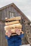 Un homme porte le groupe de bois de chauffage coupé contre le contexte de Photos stock