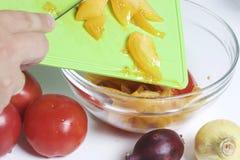 Un homme prépare une salade végétale Vide les tomates coupées en tranches de la planche à découper dans le récipient avec des lég Image stock