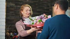Un homme prend un bouquet des fleurs d'un fleuriste banque de vidéos