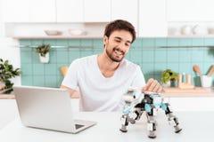 Un homme programme un robot dans la cuisine Il travaille sur un ordinateur portable gris Le robot se tient à côté de la table Photographie stock libre de droits