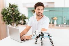 Un homme programme un robot dans la cuisine Il travaille sur un ordinateur portable gris Le robot se tient à côté de la table Photo stock