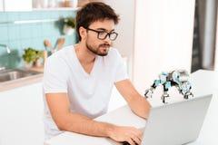Un homme programme un robot dans la cuisine Il travaille sur un ordinateur portable gris Le robot se tient à côté de la table Photographie stock
