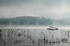 Un homme ramant son bateau dans Sangkhlaburi, Thaïlande Image libre de droits