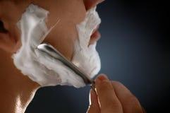 Un homme rasant le visage photo stock