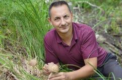 Un homme rassemble des champignons Photo stock