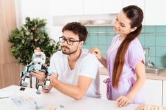 Un homme rassemble un robot dans la cuisine La femme lui parle affectueusement L'homme le gesticule  Photographie stock libre de droits