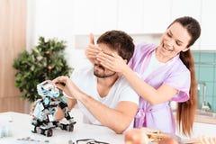 Un homme rassemble un robot dans la cuisine Son amie est venue chez lui par derrière et couvre doucement ses yeux de ses mains Image stock