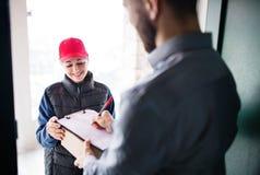 Un homme recevant le colis de la femme de la livraison à la porte image libre de droits