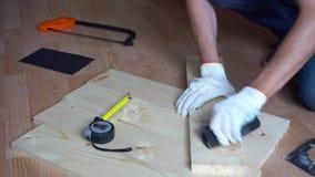 Un homme rectifie une planche en bois banque de vidéos