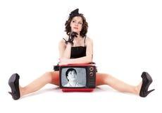 Un homme regardant sur la fille par le vieux tube de TV Images libres de droits