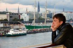 Un homme regarde de la plate-forme d'un bateau de croisière regardant ville portuaire Photos libres de droits