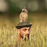Un homme regarde hors de l'herbe avec un hibou sur sa tête et regarde dans différentes directions photos stock
