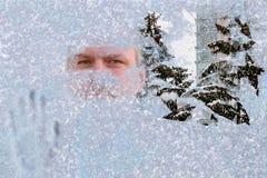 Un homme regarde par l'espace dégagé dans le verre de fenêtre congelé, image stock
