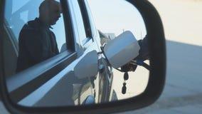 Un homme remplit une voiture d'essence banque de vidéos