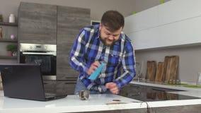 Un homme a renversé le café dans la cuisine fonctionnant derrière un ordinateur portable, le café renversé de nettoyage, lent-MOI banque de vidéos