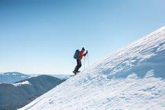 Un homme s'élève jusqu'au dessus de la montagne photos stock