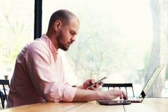 Un homme s'asseyant à une grande table en bois dans son téléphone de main Photographie stock libre de droits
