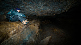 Un homme s'asseyant dans une caverne. Image stock