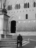 Un homme s'asseyant en dehors de la banque la plus ancienne, Sienne, Italie Photographie stock libre de droits