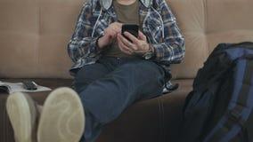 Un homme s'asseyant sur le divan emploie l'Internet dans un smartphone, à côté de lui est un grand sac à dos de touristes banque de vidéos