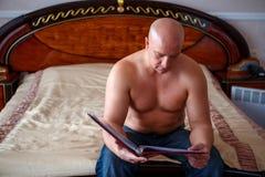 Un homme s'asseyant sur le lit et lisant un magazine photos libres de droits