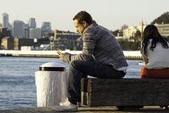 Un homme s'asseyant sur une jetée regardant son téléphone Photos stock