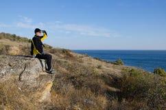 Un homme s'asseyant sur une roche Image libre de droits