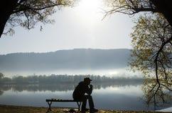 Un homme s'asseyant tranquillement près du lac Image libre de droits