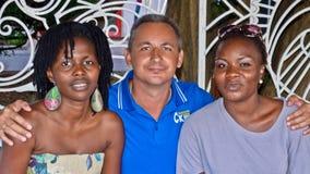 Un homme s'assied à côté de la femme de couleur de deux jeunes Photos libres de droits