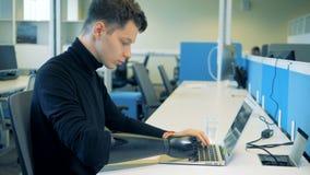 Un homme s'assied à une table, fonctionnant avec un ordinateur portable tout en utilisant une main prosthétique 4K banque de vidéos