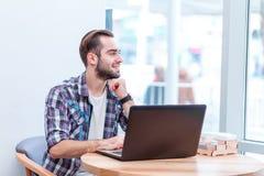 Un homme, s'assied dans un café avec un ordinateur portable ouvert et regarde la fenêtre Images stock