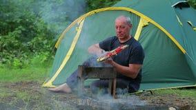 Un homme s'assied dans la forêt sur le fond d'une tente, prépare le dîner sur son brasero clips vidéos