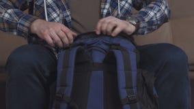 Un homme s'assied sur le divan, met des choses dans un sac à dos, les attache et laisse le cadre banque de vidéos