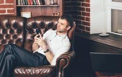 Un homme s'assied sur un sofa en cuir confortable et tient le téléphone dans des ses mains sur le fond de l'intérieur élégant de  image libre de droits
