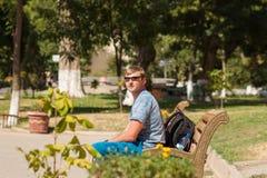 Un homme s'assied sur un banc Photographie stock