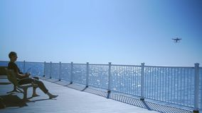 Un homme s'assied sur un banc et lance un bourdon sur la mer banque de vidéos