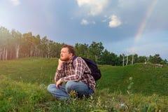 Un homme s'assied sur une colline et observer le coucher du soleil Photos stock