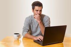 Un homme s'assied sur une table et travaille sur un ordinateur portable Image libre de droits
