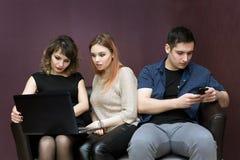 Un homme s'ennuie avec deux filles observant un film images stock