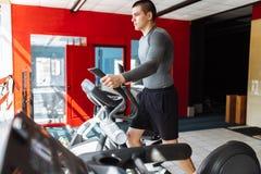 Un homme s'est engagé dans la formation sur un vélo de sports dans le gymnase, formation de matin photographie stock libre de droits