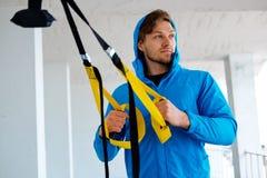 Un homme s'exerçant avec des bandes de forme physique de trx Photographie stock