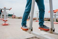 Un homme s'exerce sur l'équipement sportif dans une ville en plein air Le concept d'un mode de vie et d'une accessibilité sains d Images stock