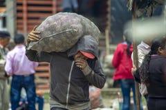 Un homme s'inquiétant un sac de pommes de terre images libres de droits