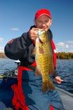 Pêche d'homme tenant la basse de Smallmouth Photographie stock