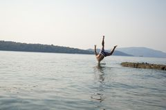 Un homme sautant dans l'eau Photographie stock