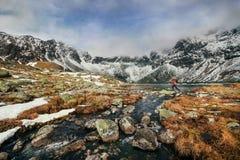 Un homme sautant à travers des roches au-dessus d'un lac dans le haut Tatras Image stock
