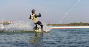 Un homme saute le sillage derrière un bateau Images libres de droits