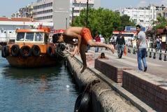 Un homme saute outre du mur de port dans la mer chez Canakkale en Turquie photo stock