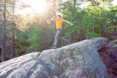 Un homme saute sur une montagne Photographie stock libre de droits